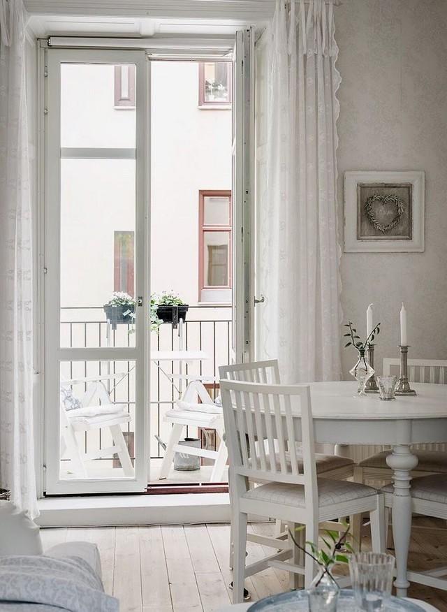 Ngay cạnh là bộ bàn ăn gỗ được trang trí lãng mạn với nến và cây xanh.