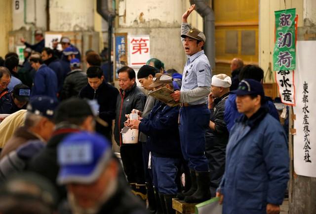 Người điều khiển giơ tay hô giá trong phiên đấu giá cá ngừ đầu năm ở chợ Tsukiji, Tokyo, Nhật Bản, ngày 5/1. Ảnh: Reuters.