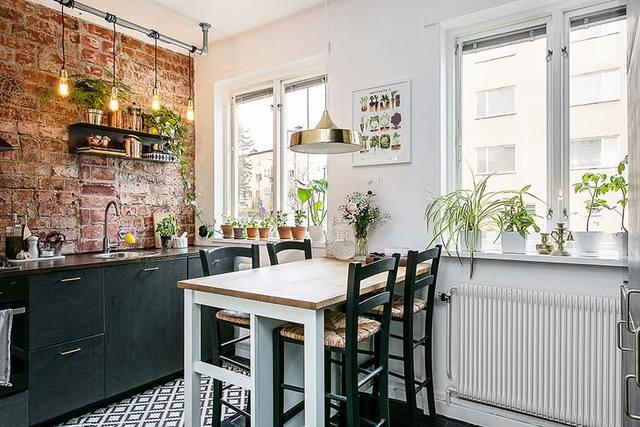 Căn hộ tuy nhỏ nhưng có lợi thế là rất nhiều cửa sổ. Trong ảnh là góc bếp ăn bừng sáng với cây xanh và bức tường thô.
