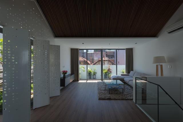 Không gian phòng khách vô cùng thoáng mát và rộng rãi với hoa nắng nhảy nhót nhờ hệ thống cửa gấp với rất nhiều những lỗ hổng hình tròn.