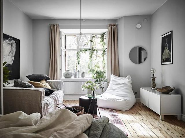 Phòng khách được bày trí đơn giản với bàn cafe nhỏ, bộ sofa êm ái kèm theo chiếc ghế lười tiện dụng màu trắng muốt.