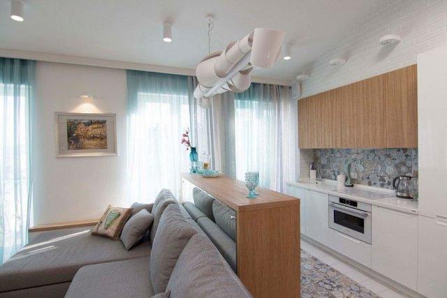 Phía sau ghế sofa là góc bếp nhỏ được bố trí gọn gàng ngăn nắp.