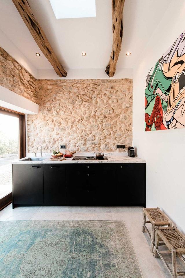 Để tăng thêm nét đẹp bình dị nhưng không kém phần gần gũi và lôi cuốn cho khoảng chức năng này, kiến trúc sư đã chọn cách tạo bức tường gần bếp để ốp đá và sơn màu vàng đất.