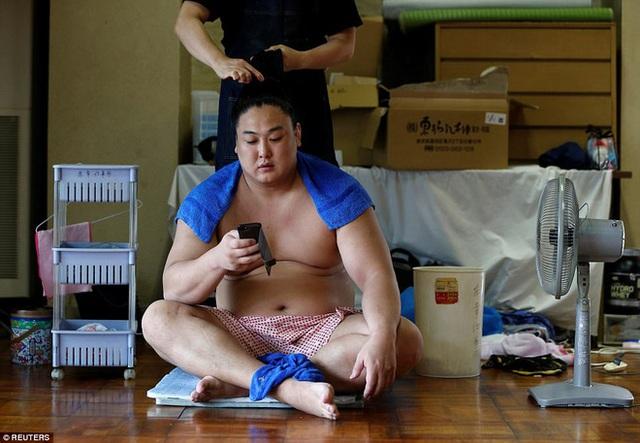 Một võ sĩ sumo đang được búi tóc đúng theo kiểu truyền thống.