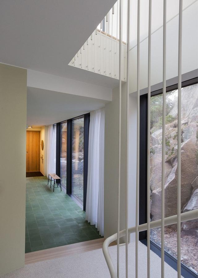 Qua bức tường kính nơi tầng 1 có thể nhìn thấy những mỏm đá lớn bao quanh ngôi nhà khiến khung cảnh trông hoang sơ và thích mắt.