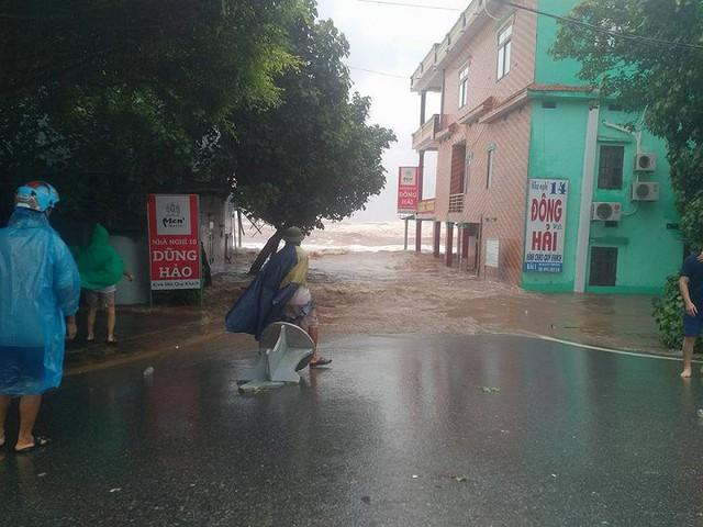 Nhiều người dân vẫn đang loay hoay trong mưa gió để chống bão số 10. (Ảnh: Phạm Tùng)