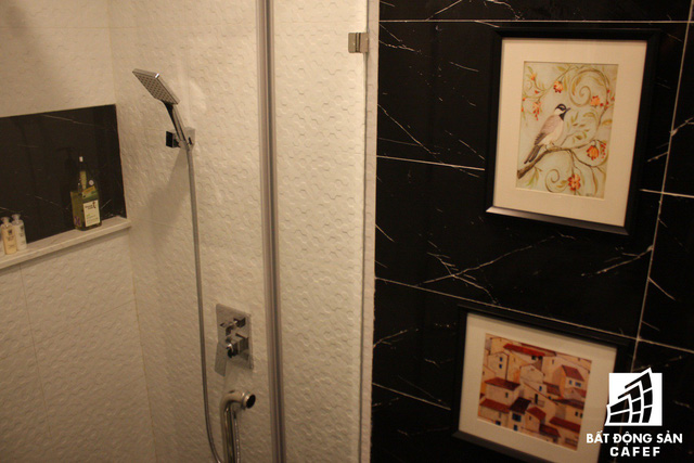 Phòng tắm được trang bị vòi tắm hoa sen hiện đại và thuận tiện với kệ để đồ ngay cạnh. Cửa vào phòng tắm còn được trang trí bắt mắt bằng những bức tranh tuyệt đẹp.