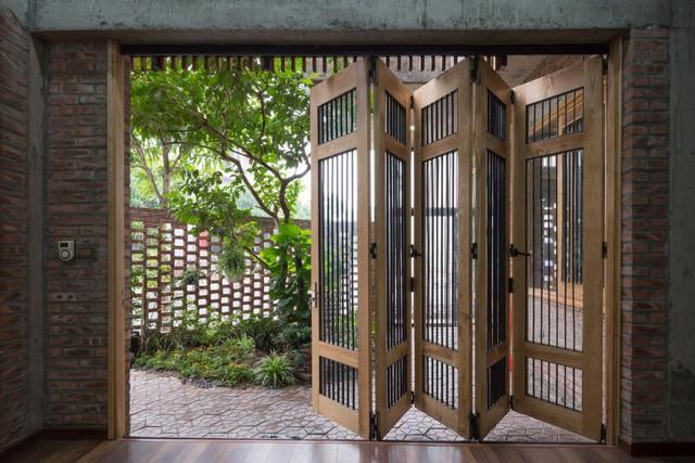 Hệ cửa lớn trước nhà được thiết kế gấp dễ đóng mở mà không hề tốn diện tích ngôi nhà.