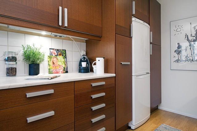 Khu bếp tuy không lớn nhưng lại rất ngăn nắp gọn gàng và đẹp mắt với những khối tủ lưu trữ bằng gỗ đậm màu nổi bật trên nền tường trắng.