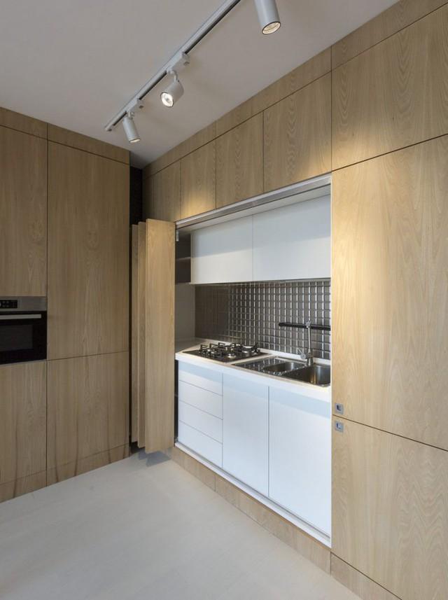 Và đây là bí mật, chỉ cần đẩy nhẹ cánh cửa là cả một đảo bếp xuất hiện ngay trước mắt. Chiếc tủ lạnh, lò vi sóng và tất cả những dụng cụ phục vụ cho việc nấu nướng đều được tích hợp trong hệ tủ này.