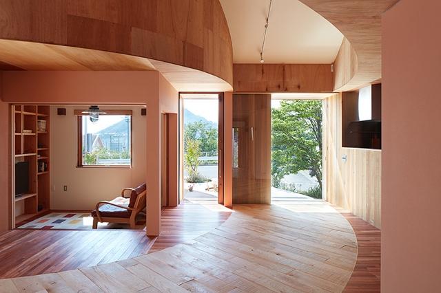Lối đi hình tròn uốn được ốp gỗ sáng màu vừa có chức năng phân chia không gian, vừa tăng tính thẩm mỹ cho ngôi nhà.
