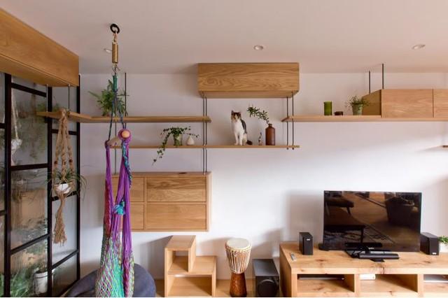 """Trên bức tường chạy dọc ngôi nhà là những kệ gỗ lên xuống so le vừa có tác dụng tạo điểm nhấn, trang trí cho ngôi nhà vừa là khu vực """"vui chơi"""" dành cho những con vật cưng trong nhà."""