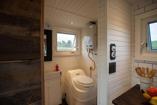 Bên trong bếp là khu vệ sinh nhỏ được thiết kế thông minh giấu gọn phía sau cánh cửa màu đen phía cuối nhà.