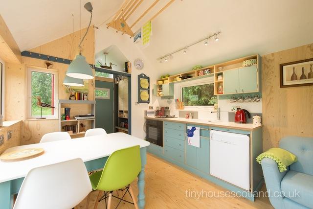 Phòng khách được bố trí đơn giản với chiếc ghế sofa xanh đặt dọc bức tường. Nối liền với không gian tiếp khách là khu bếp nhỏ sạch sẽ ngăn nắp cùng bộ bàn ăn đặt cạnh cửa sổ.