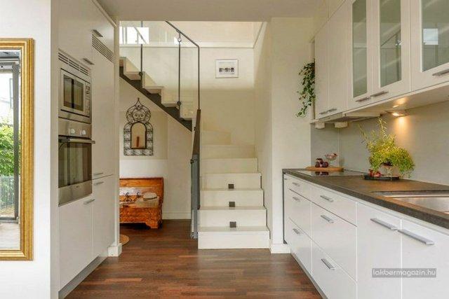 Chiếc cầu thang dẫn lên tầng 2 được bố trí rất ấn tượng với tông màu trắng. Lan can được làm bằng kính tạo vẻ thanh thoát cho căn nhà.