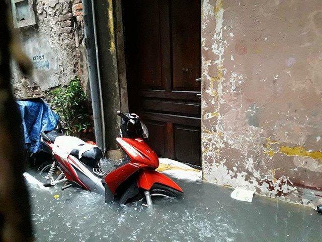Trước cửa một ngôi nhà trên phố Tạ Hiện nước ngập qua bánh xe. (Ảnh: Trần Quốc Đạt)