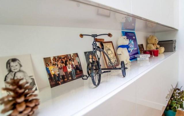 Không chỉ lấy màu xanh - trắng làm chủ đạo, phòng khách còn được trang trí thêm nhiều tranh ảnh gia đình và nhiều đồ lưu niệm đẹp tạo không gian vui tươi mà vẫn không làm rối mắt người dùng.