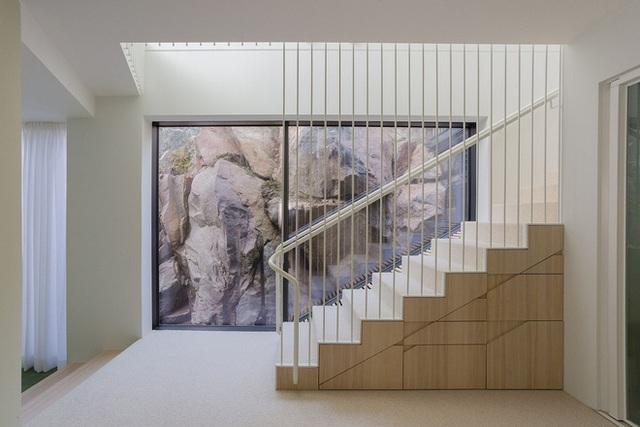 Bức tường kính nơi chân cầu thang dẫn lên tầng 2 với những mõm đá khổng lồ trông hệt như một bức tranh lớn.