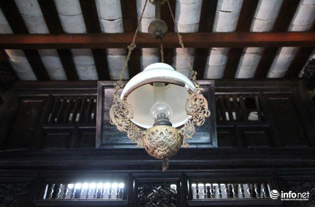 Một chiếc đèn cổ, chạm khắc tinh xảo được gia đình sử dụng.