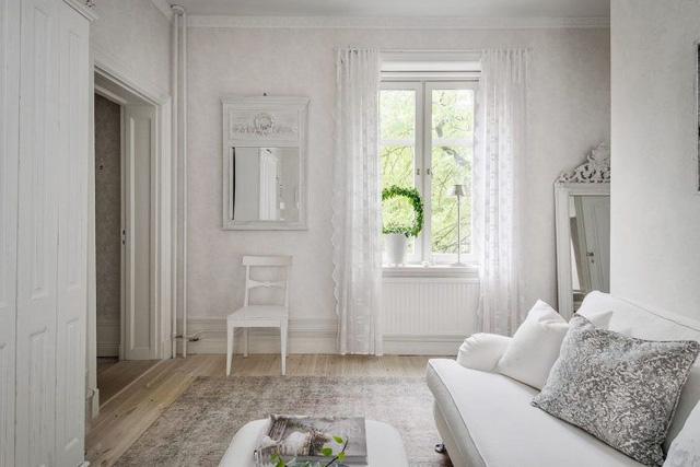 Điểm ấn tượng đặc biệt trong căn hộ này là hầu hết nội thất đều mang tông màu trắng chủ đạo. Tuy nhiên nó lại không hề mang đến cảm giác lạnh và tẻ nhạt nhờ có những chi tiết nhấn nhá như cây xanh và những chiếc gối ôm tông xám.