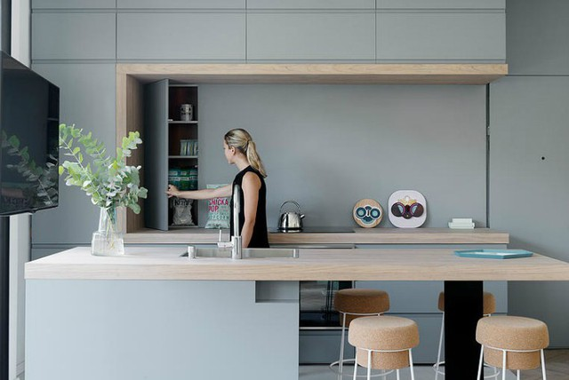 Đến khu vực nhà bếp, bạn sẽ được thấy cách tổ chức hết sức khoa học và gọn gàng. Toàn bộ tủ bếp được thiết kế có cánh để bảo quản dụng cụ nhà bếp luôn sạch sẽ, tránh bụi bẩn. Bàn ăn được thiết kế ngay cạnh rất thuận tiện cho việc nấu nướng của chủ nhà.