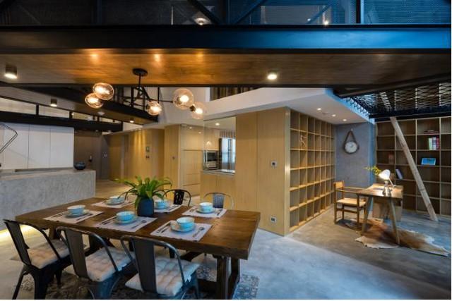 Khu vực sau lưng bếp là góc đọc sách. Nơi đây được thông lên cả tầng 2 nhờ một cái thang nhỏ cạnh giá sách cao sát trần.