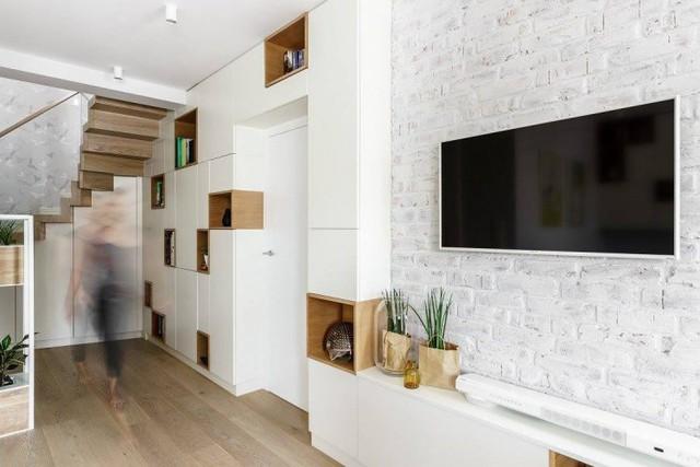 Trong căn hộ mọi không gian đều được thiết kế nhằm tối ưu diện tích sử dụng. Chiếc tivi lớn được gắn cố định vào tường để tiết kiệm diện tích. Ngay cạnh là chiếc hệ thống tủ gỗ đựng đồ vô cùng tiện nghi vắt ngang qua cửa phòng ngủ của bố mẹ.