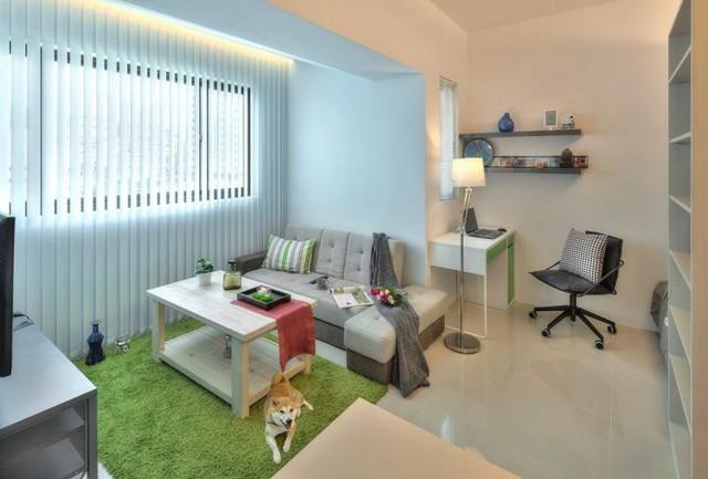 Khu tiếp khách được bố trí đơn giản với chiếc ghế sofa dài cùng bàn trà gỗ. Phía đối diện là chiếc ti vi gắn cố định vào tường để tiết kiệm diện tích.
