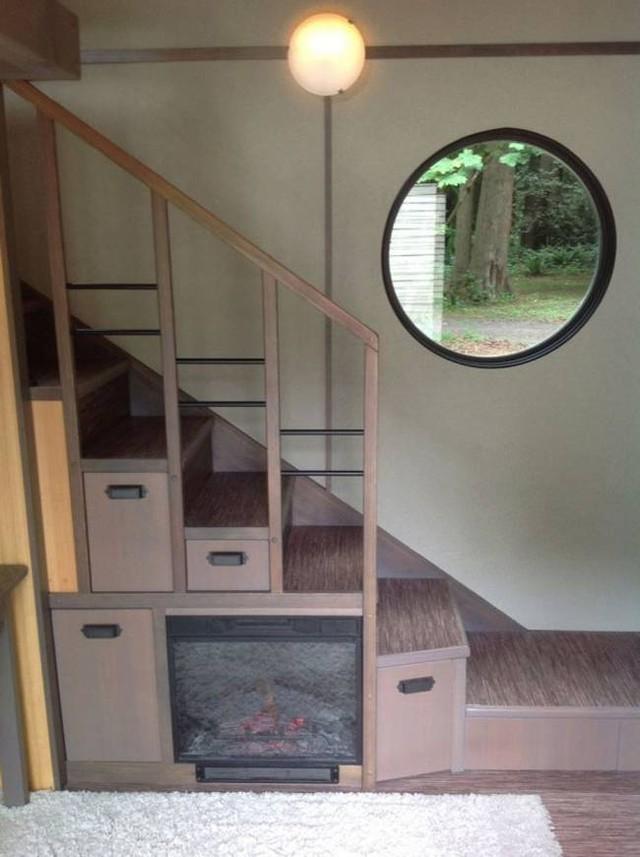 Chiếc cầu thang nhỏ dẫn lên gác xep được thiết kế vô cùng tinh tế và đẹp mắt. Mỗi bậc cầu thang là những ngăn kéo chứa đồ lý tưởng. Đặc biệt nơi đây còn được tô điểm bắt mắt bởi một cửa sổ tròn.