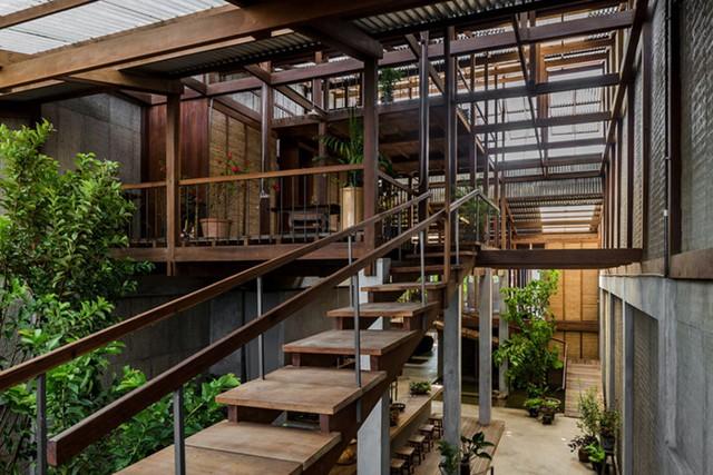 Không gian tầng 2 ngôi nhà được nối liền bằng một cầu thang gỗ với tay vịn bằng sắt.