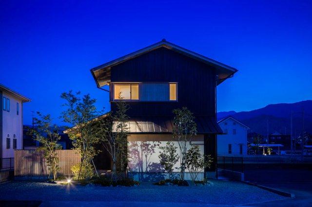Ngôi nhà vượt trội giữa khu dân cư có ánh sáng điện về đêm.