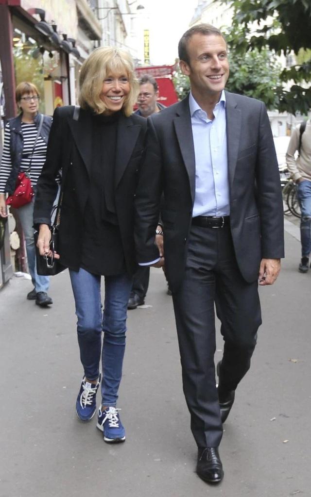 Phu nhân Tổng thống Pháp sánh đôi cùng chồng trong trang phục quần jean, giày thể thao và áo khoác đen đơn giản, khỏe khoắn và năng động.