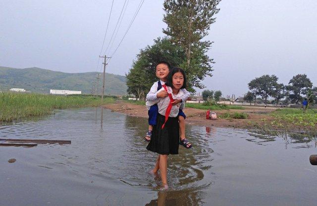 Hai đứa trẻ cõng nhau tới trường ở Tumangang. Triều Tiên là một trong những quốc gia ít ỏi trên trái đất sở hữu công nghệ chế tạo vũ khí hạt nhân. Tuy nhiên, trên lĩnh vực kinh tế, Triều Tiên là cái tên hiếm khi được nhắc tới.