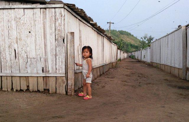 Một đứa trẻ chơi trên con đường đất nằm giữa hai hàng rào gỗ.