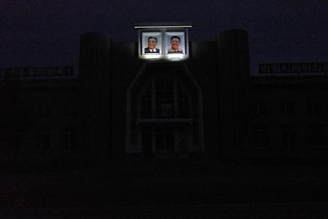 Vào buổi đêm, hai bức tượng được chiếu sáng rực rỡ. Những tòa nhà nằm trong bóng tối.