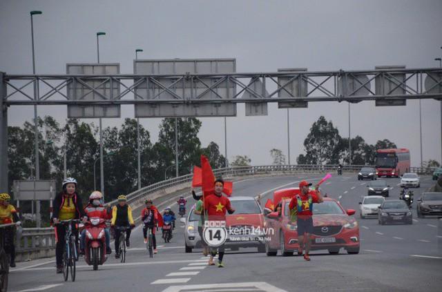 Chùm ảnh: Người hâm mộ cầm cờ Tổ quốc, chạy bộ ra sân bay Nội Bài để đón U23 Việt Nam  - Ảnh 1.