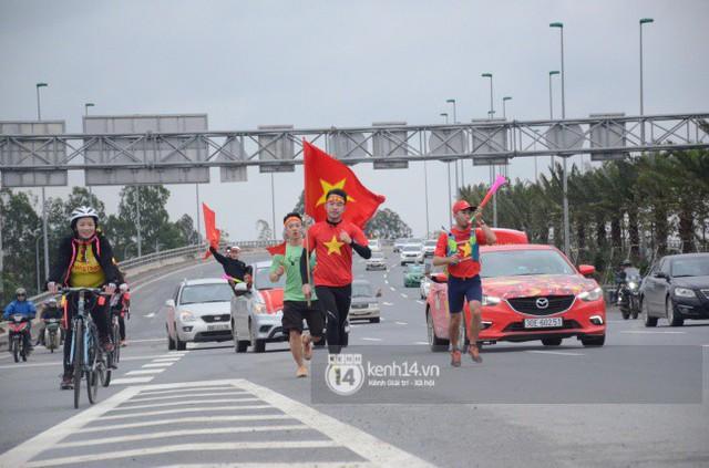 Chùm ảnh: Người hâm mộ cầm cờ Tổ quốc, chạy bộ ra sân bay Nội Bài để đón U23 Việt Nam  - Ảnh 4.