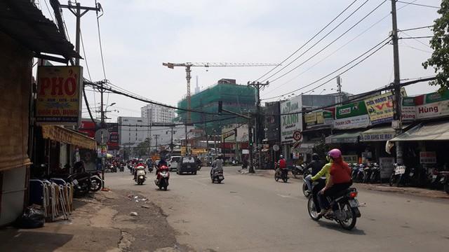 Cận cảnh những cần cẩu công trình dài hàng chục mét treo lơ lửng trên đầu người đi đường ở Sài Gòn - Ảnh 1.