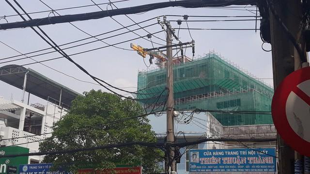 Cận cảnh những cần cẩu công trình dài hàng chục mét treo lơ lửng trên đầu người đi đường ở Sài Gòn - Ảnh 2.