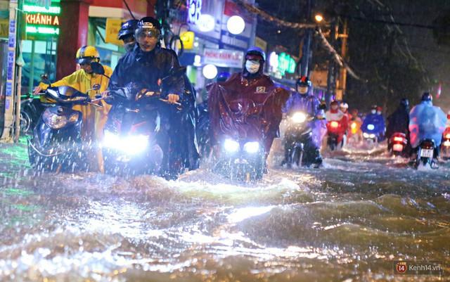 Học sinh, dân công sở khốn khổ vì nước ngập lút bánh xe trong cơn mưa kéo dài đến đêm ở Sài Gòn - Ảnh 2.