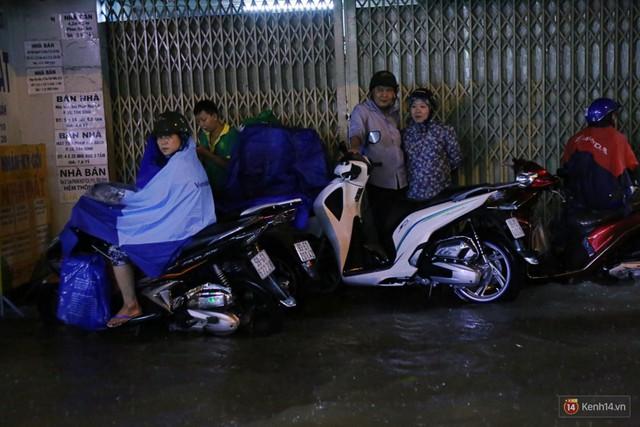 Học sinh, dân công sở khốn khổ vì nước ngập lút bánh xe trong cơn mưa kéo dài đến đêm ở Sài Gòn - Ảnh 13.