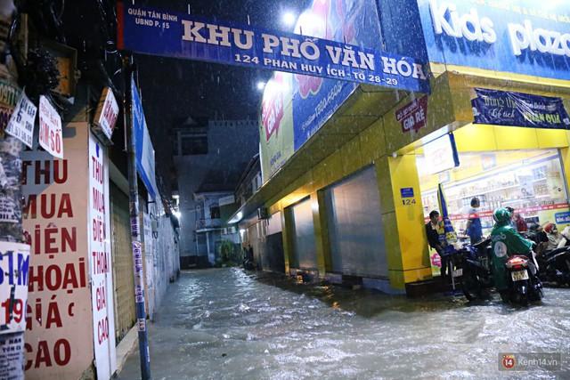 Học sinh, dân công sở khốn khổ vì nước ngập lút bánh xe trong cơn mưa kéo dài đến đêm ở Sài Gòn - Ảnh 4.