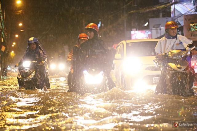 Học sinh, dân công sở khốn khổ vì nước ngập lút bánh xe trong cơn mưa kéo dài đến đêm ở Sài Gòn - Ảnh 5.