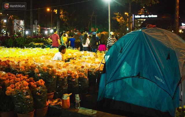 Chùm ảnh: Sợ mất trộm, nhiều gia đình tiểu thương dựng lều mắc võng, thay phiên nhau thức đêm để canh hoa Tết - Ảnh 1.