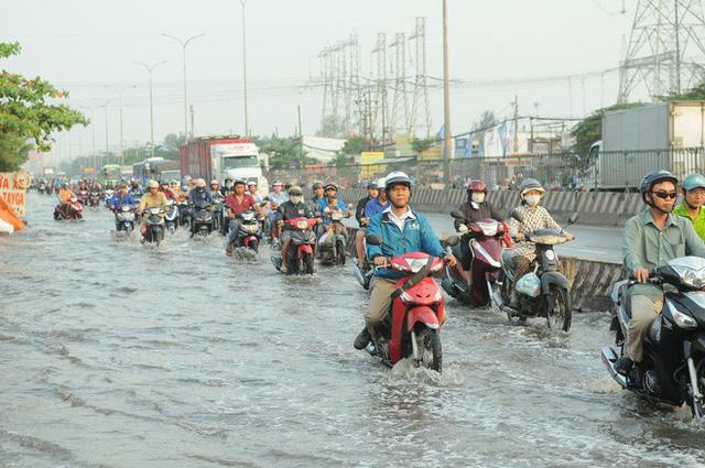 Nước dâng ngập lút bánh xe trên nhiều tuyến đường ở Sài Gòn - Ảnh 1.