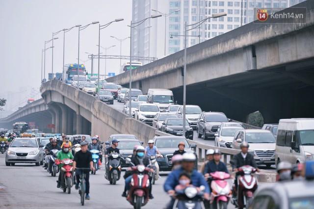 Người dân mang theo hành lí chất trên nóc ô tô, xe máy đổ về Hà Nội và Sài Gòn sau kì nghỉ Tết Nguyên đán kéo dài 1 tuần - Ảnh 1.
