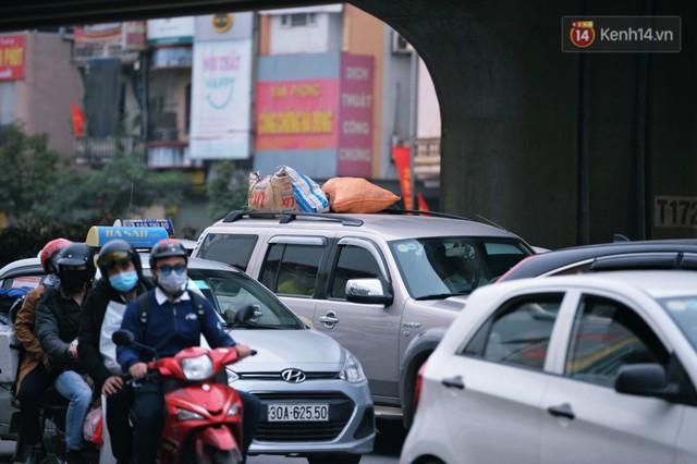 Người dân mang theo hành lí chất trên nóc ô tô, xe máy đổ về Hà Nội và Sài Gòn sau kì nghỉ Tết Nguyên đán kéo dài 1 tuần - Ảnh 5.