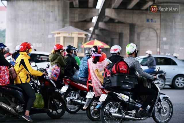 Người dân mang theo hành lí chất trên nóc ô tô, xe máy đổ về Hà Nội và Sài Gòn sau kì nghỉ Tết Nguyên đán kéo dài 1 tuần - Ảnh 9.