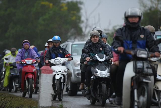 Ảnh: Tắc đường dài 3km, người dân ùn ùn đội mưa đi bộ vào chợ Viềng - Ảnh 1.