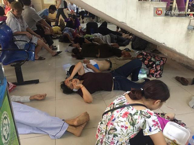 Ảnh: Người nhà bệnh nhân vạ vật gần hành lang, dưới bóng cây trong bệnh viện để tránh nắng nóng đỉnh điểm trên 40 độ ở Hà Nội - Ảnh 1.